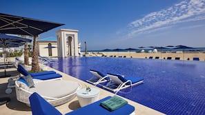 Piscine couverte, piscine extérieure, parasols de plage, chaises longues