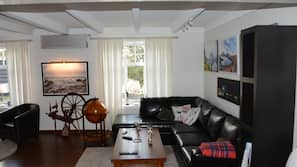 En 40-tommers flatskjerm-TV med kabel-kanaler samt peis