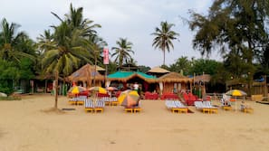 On the beach, white sand, sun-loungers, beach umbrellas
