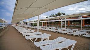 Privatstrand, schwarzer Sandstrand, Liegestühle, Sonnenschirme