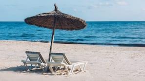 Na praia, espreguiçadeiras, guarda-sóis, bar na praia