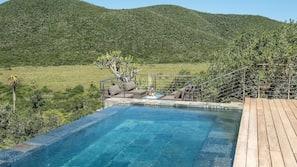 Una piscina al aire libre, una piscina con borde infinito, sombrillas