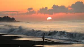 Di pantai, pasir hitam, kursi berjemur, dan payung pantai