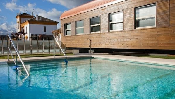 Una piscina al aire libre de temporada, sombrillas