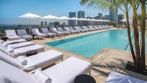 Una piscina al aire libre, cabañas de piscina (de pago), tumbonas