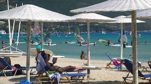 On the beach, sun-loungers, beach umbrellas, windsurfing
