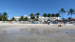 Na praia, areia branca, barracas de praia de cortesia