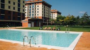 Una piscina cubierta, una piscina al aire libre de temporada, tumbonas