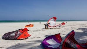 Na praia, areia branca, espreguiçadeiras, prática de mergulho autônomo
