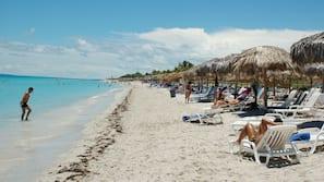 Sulla spiaggia, sabbia bianca, lettini da mare, teli da spiaggia