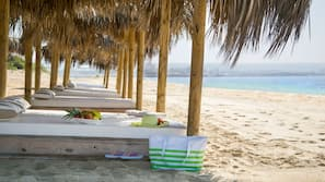 På stranden, vit sandstrand, solstolar och parasoller