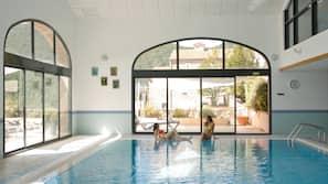 Piscine couverte, piscine avec cascade, chaises longues