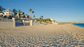Na praia, espreguiçadeiras, toalhas de praia, massagens na praia