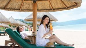 在海灘附近、白沙、躺椅、太陽傘