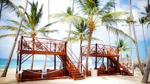 On the beach, white sand, sun loungers, beach umbrellas