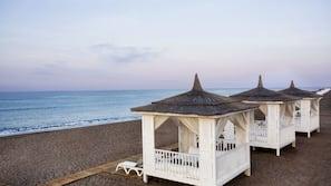 Plage privée, cabines (en supplément), chaises longues, parasols