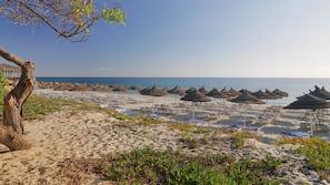 Na praia, barracas de praia de cortesia, espreguiçadeiras, guarda-sóis