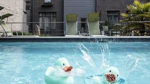 Een seizoensgebonden buitenzwembad, ligstoelen bij het zwembad