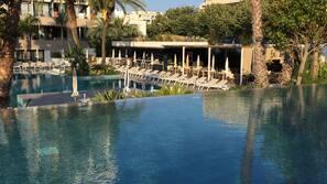 Een binnenzwembad, 3 buitenzwembaden, ligstoelen bij het zwembad