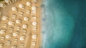 Vlak bij het strand, ligstoelen aan het strand, parasols