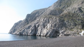On the beach, black sand, sun-loungers, beach umbrellas