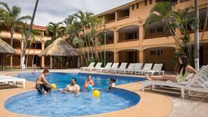 Una piscina al aire libre, tumbonas, socorrista en las instalaciones