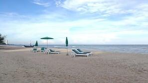 Nära stranden, vit sandstrand, solstolar och parasoller