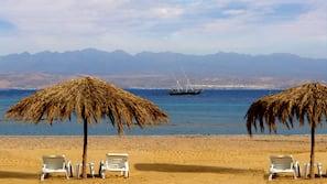 Na praia, guarda-sóis, toalhas de praia, massagens na praia