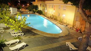 Una piscina al aire libre, sombrillas, tumbonas