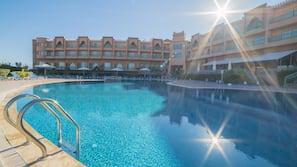 Una piscina al aire libre, sombrillas