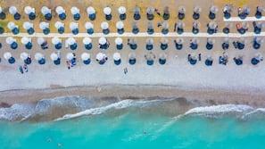 Beach nearby, beach umbrellas, beach towels, windsurfing