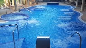 Una piscina al aire libre de temporada, tumbonas