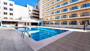 Een seizoensgebonden buitenzwembad en ligstoelen