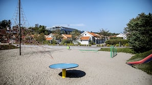 På stranden, solsenger, strandhåndklær og sandvolleyball
