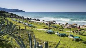 Praia particular, espreguiçadeiras, guarda-sóis
