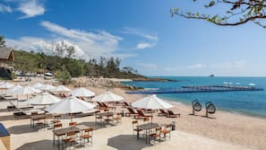 Aan een privéstrand, wit zand, parasols, strandlakens