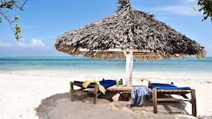 Plage privée, sable blanc, parasols, serviettes de plage