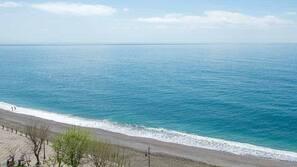 Sulla spiaggia, sabbia scura, lettini da mare, ombrelloni