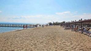 Een privéstrand, ligstoelen aan het strand, parasols