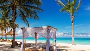 Am Strand, weißer Sandstrand, Liegestühle, Sonnenschirme