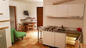 Frigorífico grande, placa de cocina y utensilios de cocina