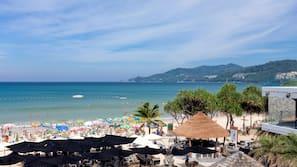 Di pantai, pasir putih, handuk pantai, dan bar pantai