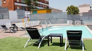 Una piscina al aire libre de temporada, una piscina con cascada