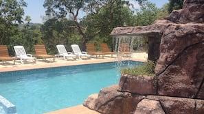 Una piscina al aire libre, una piscina con cascada, sombrillas, tumbonas