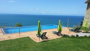 Seasonal outdoor pool, an infinity pool, pool umbrellas, pool loungers