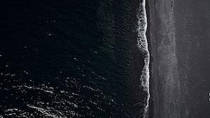 Plage à proximité, sable noir, chaises longues, serviettes de plage