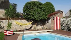 Een seizoensgebonden buitenzwembad, parasols voor strand/zwembad