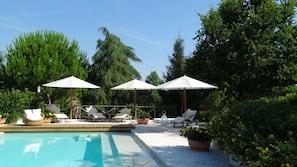 Piscina all'aperto, una piscina a sfioro, ombrelloni da piscina, lettini