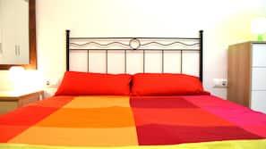 2 dormitorios y tabla de planchar con plancha