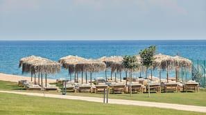 In Strandnähe, schwarzer Sandstrand, Liegestühle, Sonnenschirme